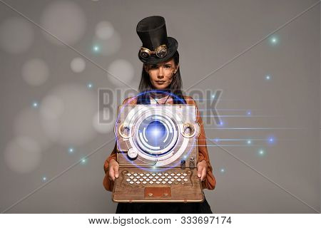Steampunk Woman In Top Hat With Goggles Showing Vintage Laptop With Glowing Digital Illustration Iso