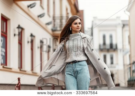 Chic Modern Young Woman With Brown Hair In A Stylish Long Trench Coat In A Knitted Sweater In A Blue