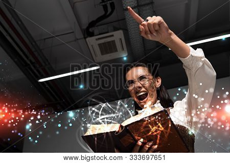 Low Angle View Of Angry Steampunk Woman Holding Open Book With Fairy Glowing Illustration, Screaming