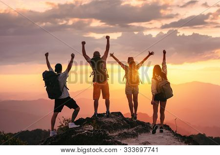 Happy Friends Hikers Or Tourists Stands With Raised Arms On Mountain Top Against Mountains And Looki