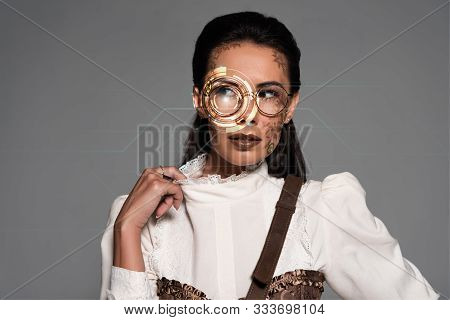 Pensive Steampunk Woman With Digital Illustration On Face Looking Away Isolated On Grey