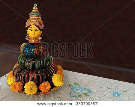 Bangle Doll, is being adorned with colourful bangles around her. Very artistic original creation.Symbol of bangles ritual of ladies in Indian weddings. Selective focus of the object. poster