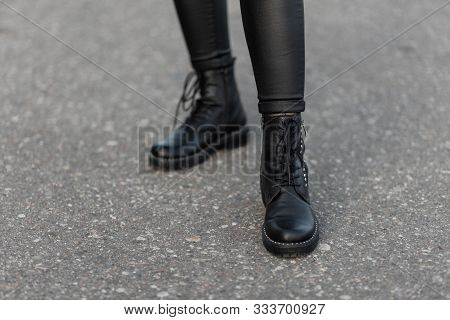 Close Up Of Female Legs In Black Trendy Leggings In Leather Stylish Boots. Fashionable Woman Walks O