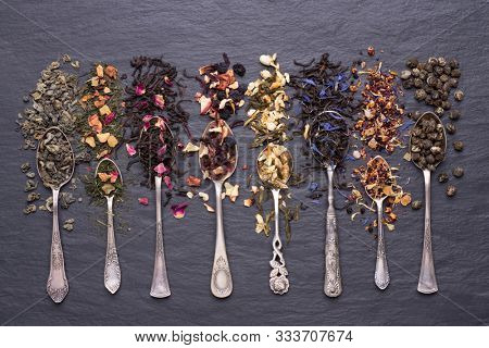 Assortment of dry green, black and fruit teas leaves in silver spoons on black stone background