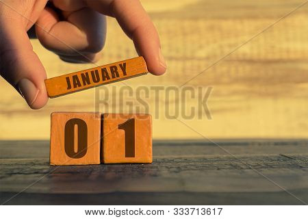 January 1st. Day 1 Of Month, Calendar On A Wooden Cube. A Womans Hand Puts The Name Of The Month On