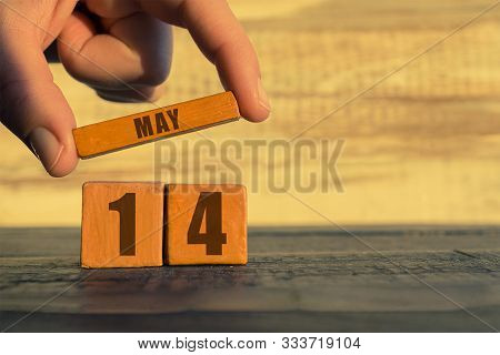 May 14th. Day 14 Of Month, Calendar On A Wooden Cube. A Womans Hand Puts The Name Of The Month On Th