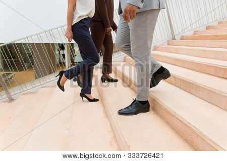Businesspeople Walking Upstairs And Downstairs. Legs And Feet Of Business Man And Women Wearing Form