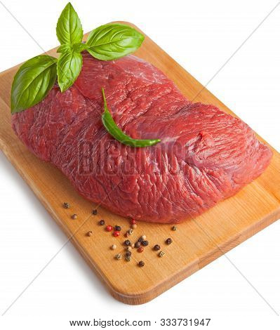 Raw Piece Of Beef With Spices On A Board, Isolated On A White Background. Selective Focus.