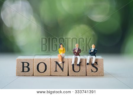Miniature People : Staff Sitting On Wooden Block Of Bonus For Waiting Bonus. Bonus Prize Profit Ince