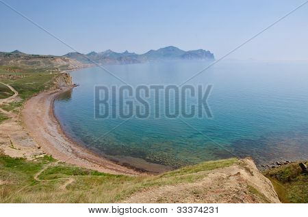 A landscape on sea. The rocks, cliffs, green cape, azure water.