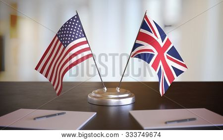 Usa And British Flags On Table. Negotiation Between United Kingdom And United States. 3d Rendered Il