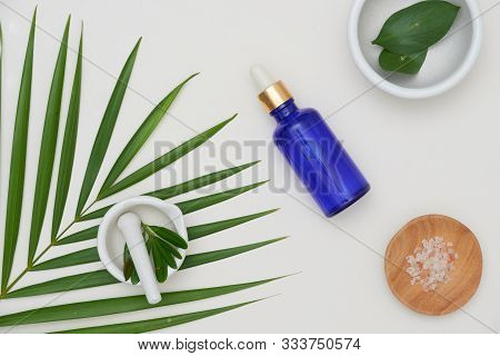 Blue Serum Bottle With Martar, Massage Salt, Herb On White Background. Spa And Beauty Organic Concep