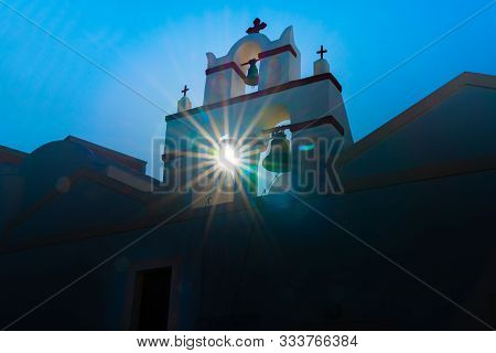 Traditional Greek Church Bell Tower Back-lit By Sun With Starburst And Lens Flare.