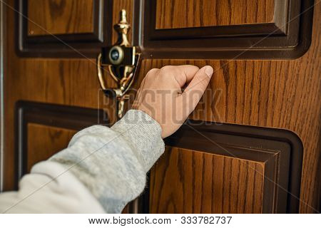 Hand Knocks On The Wooden Door. Private Property Visitor Relative Guest Kin Get Lost.