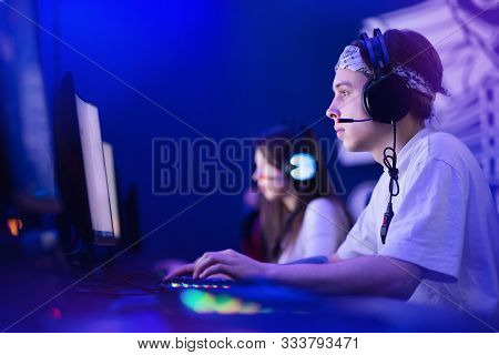 Team Professional Gamer Playing Tournaments Online Games Computer With Headphones, Red And Blue