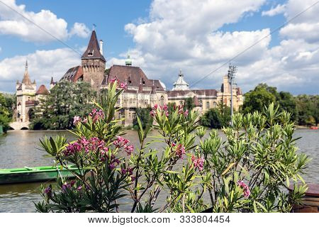 Budapest Vajdahunyad Castle Viewed From Its Lakeside And People With Oleander Flowers