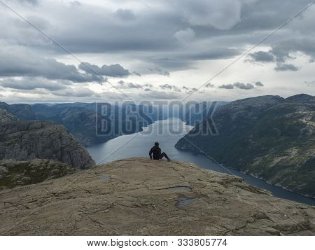 Hiker Woman Admiring View On Fjord Lysefjord From Preikestolen Massive Cliff, Famous Norway Viewpoin