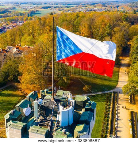 Hluboka nad Vltavou / Czech Republic - October 28, 2019: Czech flag waving over Hluboka Castle in national holiday.  Day when independent Czechoslovakia was officially founded in 1918.