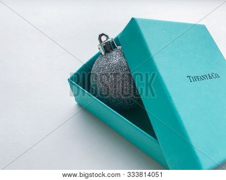 Original Box From The Jewelry Brand Tiffany And Co. Inside Of Which Is A Shiny Silver Christmas Ball
