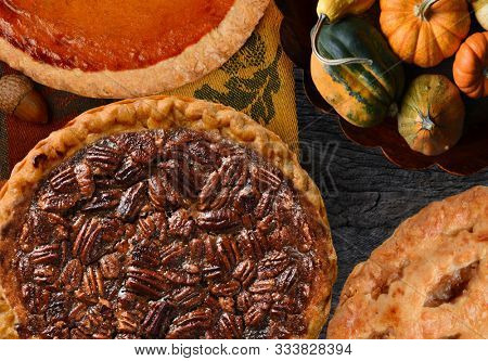 Pecan, Pumpkin, and Apple Thanksgiving Holiday Pies on a rustic table with decorative gourds.
