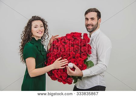 She Said Yes. Gorgeous Girl Accepting A Ring And Flowers From Her Boyfriend.