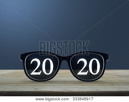 2020 White Text With Black Eye Glasses On Wooden Table Over Light Blue Gradient Background, Business
