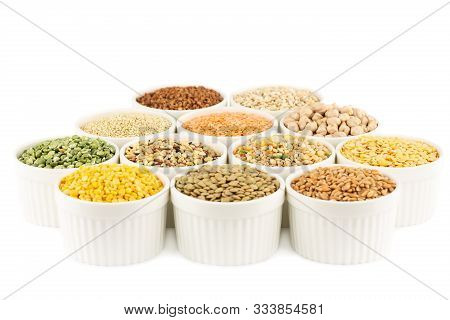 The Collection Of Different Groats In The White Ceramic Bowls Isolated On A White Background. Split
