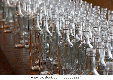 Glassworks. Glass Industry. Many Glass Bottles On An Industrial Conveyor.