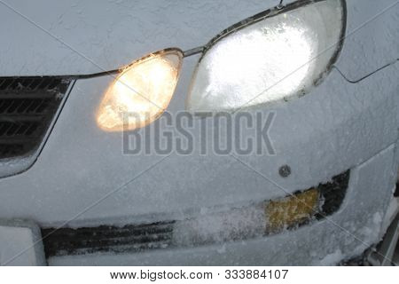 Car Headlights Covered With Frost And Slush Snow During Winter Blizzard. Bad And Extreme Weather Con