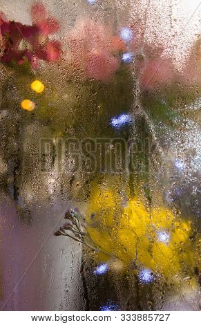 Flowers And Light Garlands Behind The Wet Glass. Moist Window. Water Drops On The Glass. Blurred Lig
