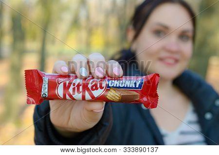 Kharkov, Ukraine - October 21, 2019: A Young Caucasian Brunette Girl Shows Kit Kat Chocolate Bars In