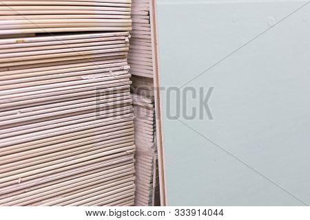 Gypsum Plasterboard In The Pack. The Stack Of Gypsum Board Preparing For Construction. Pallet With P