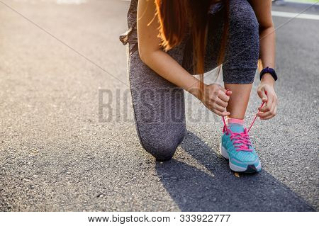 Woman Runner Tying Running Shoes Before Run For Exercise In The Morning. Woman Runner Checking Shoe