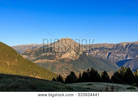 Pedraforca Mountain With Blue Sky And Green Mountains With Fir Trees