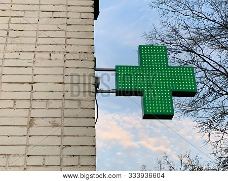Urban Pharmacy Or Drug Store Sign, Led Display Green Cross On The Wall In The City Street, Copy Spac