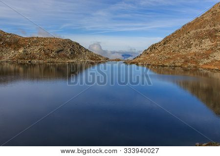 Reflection Of The Mountains In The Great Lake Of Pessó. Nature Concept