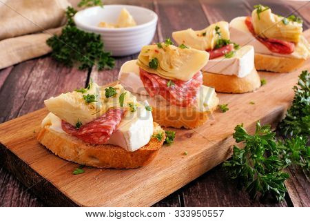 Crostini Appetizers With Brie Cheese, Salami And Artichokes. Close Up On A Serving Board Against A W