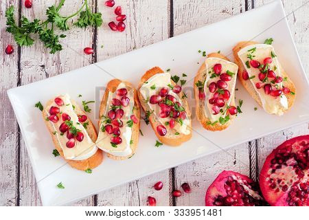 Holiday Crostini Appetizers With Brie Cheese, Pomegranates And Parsley. Top View On A Serving Plate