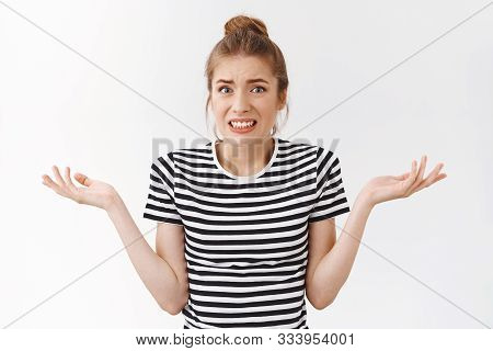 Girl Feeling Sorry And Guilty For Causing Trouble, Squinting And Shrugging With Hands Spread Sideway