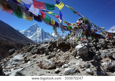 Sagarmatha national park, Nepal - May 22, 2019: Everest trek, Buddhist praying flags in the begining of tombstones area near Dughla (4620 m) with view of Ama Dablam (6856 m) in Himalayas mountains