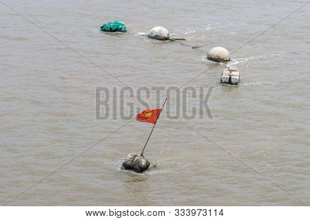 Long Tau River, Vietnam - March 12, 2019: Makeshift Buoys On Brown Water, One With Vietnamese Nation