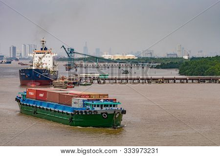 Long Tau River, Vietnam - March 12, 2019: River Container Boat Sails On Brown Water In Front Of Phuo