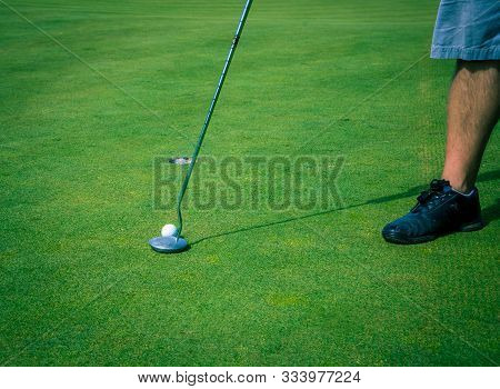 Left Handed Golfer Preparing To Putt On The Green