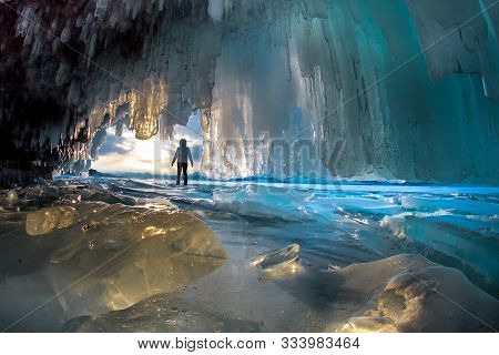 Surreal Landscape With People Exploring Mysterious Ice Grotto Cave. Outdoor Adventure. Family Explor