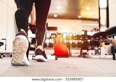 A Women Wear Sport Shoes. Full Length Portrait Of A Athletic  Women Stretching At Sport Gym.
