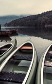 Canoes on lakeshore in cold foggy autumn morning in Ribcev laz, Slovenia poster