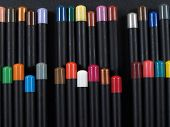 Artist pencils with identifying colored tops arranged against a black background. poster