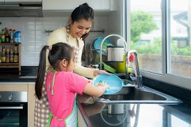 Beautiful Asian Mother And Daughter Having Fun While Washing Dishes Together With Detergent On Sink