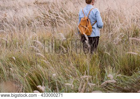 A Young Woman With A Backpack On Her Back Walks Through The Autumn Field. Concept Slow Life.