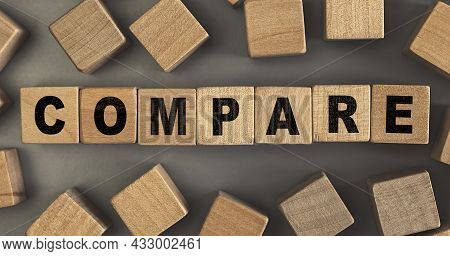 The Word Compare On Small Wooden Blocks At The Desk. Conceptual Photo. Top View
